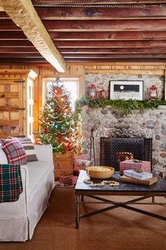 Iconic tartan adds instant warmth to a Christmas-inspired cabin's living room. From throw pillows to gift wrap, the preppy pattern adds a little polish to the otherwise understated space. For the tree, a simple popcorn garland, glass ball ornaments, and a wooden crate in lieu of a tree skirt reinforce the home's-stuck-in-time vibe. The fir garland above the mantel and solo sprigs of pine found in vases throughout the house also add an organic element.
