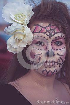 Girl dressed as Joker in  sugar skull day of the dead makeup for Halloween.