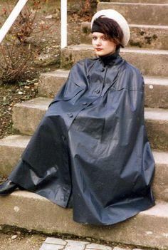 Junges Mädel im hoch geschlossenem Kleppercape auf den Stufen sitzend