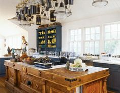 French craftsmen made the butcher-block island. The vintage light fixtures, the pot rack, and many of the old English milk pails hanging from it are from Ann-Morris Antiques. German silver sink through Joanne Hudson Associates.   - HouseBeautiful.com
