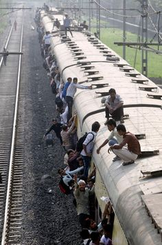 Commuters sit on the roof of an overcrowded train in Mumbai.