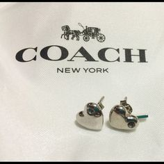Coach Sculpted Heart Stud Earrings  Brand  100% authentic Coach Pave Sculpted Heart Stud Earrings- Silver plated brass. True objects of affection, these polished heart earrings are beautifully plated in precious metal and adorned with shimmering crystals. One is finished with a petite Coach hangtag charm for a touch of signature style. Includes: a white Coach pouch, jewelry care booklet and gift box. Fast Shipping Coach Jewelry Earrings