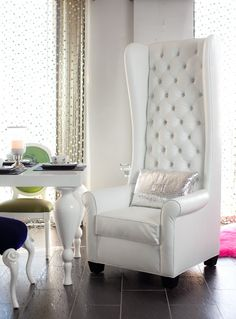 TALL WINGBACK CHAIR - Whether you're a rockstar or a glamazon, this chair is for you. The high back is fun and interesting and makes it a dramatic addition to your house. The wings enclose you slightly when seated, making the chair extremely cozy and comfortable to sit in. It is then finished off with a generous helping of dazzling Swarovski crystals that turn up the glamor and sparkle in the light. This chair brightens up and adds some fun to any room.  As with many of our items, it can be…