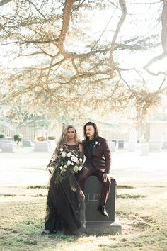 Los angeles halloween inspired wedding shoot at the mountain view cemetery bride black wedding gown with high neckline and lace detail with black sheer veil holding white and dark red floral bridal bouquet with groom burgundy tuxedo with black dress shirt and black faux leather bow tie sitting on tombstone