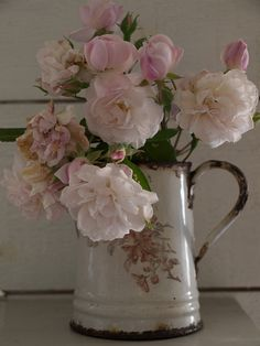 An old rose bouquet in a vintage enamel jug