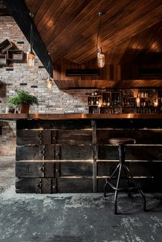 rustic industrial bar interior, rustic industrial interior, exposed concrete floor, brick wall, wood ceiling, reclaimed wood bar, metal stools, sherwin williams sealskin, dark bronze, dark brown, blackish-brown, brownish-black, warm black