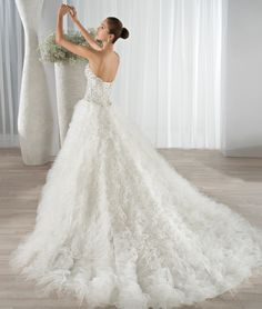 This extravagant ball gown features a beaded bodice with a sweetheart neckline, Basque waist and back lace-up closure.  The tulle ruffled skirt transitions to a Chapel train.