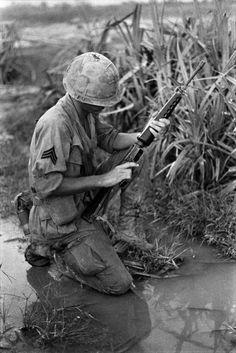 Um sargento ajoelha-se no chão molhado e verifica o seu M16. Nome, data e local desconhecido.