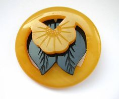This vintage carved bakelite button is in very good/excellent condition. It is a two piece coloured button with a butterscotch outer and a black inner. Measuring approx. 2 inches diameter Sold for $48 in Oct. 2013