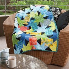 Take two matching packs of charm squares - or bits and pieces from your stash. Mix in some coordinating solids and a black tone-on-tone. Cut them into squares and triangles, join them together and you have a recipe for this wonderful quilt pattern by Sharon McConnell.