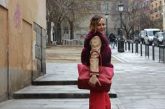 Pantalón en rojo, cazadora en tostado, chaleco en piel fucsia, bolso en rosa y rojo, coleta, ondas,