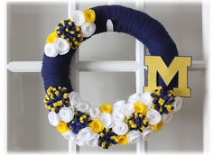 University of Michigan Wolverines Yarn Wreath by TheLandofCraft, $47.75 - I can make this! Blue yarn and yellow and white felt flowers like baby's headband flowers. Easy!  ~LK
