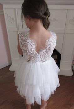This is a beautiful 3 tiered white and ivory tutu dress. The elegant bodice is white stretch lace embellished with a beautiful pearl and lace applique. The tutu skirt has 3 tiers. The skirt can be ordered in white, pink, red or ivory. It has a V neck back with unfinished lace along