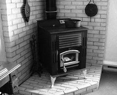 stove sitting in a corner on a brick hearth with ventilated brick on both adjacent walls. The brick creates a non-combustible surface by the stove.