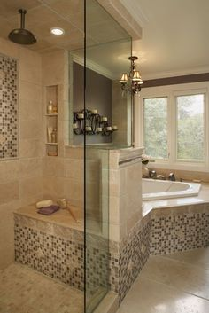 clear shower doors with tiled seat in shower round tub with windows above. Showerhead comes out of the ceiling.