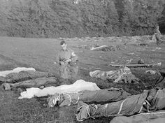 Army Chaplain Francis L. Sampson of Sioux Falls, S.D., gives absolution to American paratroopers killed in action, in Saint Marie Dumont, France, U.S. Army Photo, 7 June 1944 (Note that bodies are wrapped in parachutes)