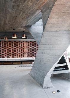 Riverside concrete pavilion by NE-AR houses a fireplace inside a twisted column