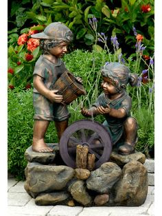Two adorable children play among a water wheel.