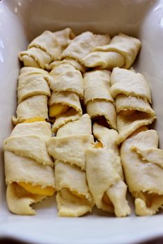 Peach crescent dumplings-2 cans Crescent Rolls 16 whole Frozen Peach Slices 1-1/2 stick (3/4 Cup) Butter 1-1/4 cup Sugar 1 teaspoon Vanilla Extract  Ground Cinnamon, For Sprinkling 1 can Sprite, 7-Up, Or Mountain Dew  Extra Butter, For The Pan