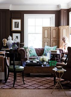 The dark walls, tufted sofa, leather wing back and opulent decor make this space beautifully masculine