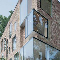 A empresa de arquitetura NADAAA de Boston remodelou uma residência de Washington DC dos anos 20 estendendo o sótão, acrescentando grandes janelas e usando folhas de madeira compensada para organizar o layout interno. Fachada de prédio em vidro e tijolo a vista.