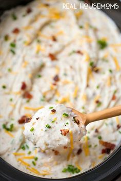 A big spoonful of Slow Cooker Loaded Mashed Potatoes being taken form the crock pot for serving