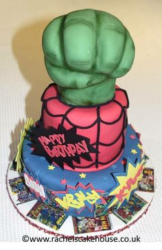 Marvel themed birthday cake, with The Hulk's hand, spider man themed middle and printed comic front covers and iced sound effect on the bottom