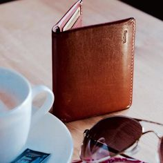 """""""All a girl needs. Bellroy slim sleeve wallet (worn from years in the back pocket of my Levis) Oakley shades and coffee."""" #mybellroy via @juliarevitt #slimsleeve #carrybetter"""