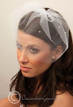 A soft birdcage veil made of illusion with a cut edge adorned with white or ivory pearls. The illusion is 9 inches long. Length 9 inches Width 9 inches Stones