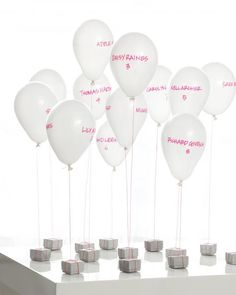 Help your reception take flight with floating escort cards that double as centerpieces once guests find their tables. On your wedding day, have a few friends fill 5-inch white balloons with helium (you can rent a tank from a party store). Once they're inflated, add guests' names and table numbers with a paint pen, tie on matching embroidery thread, and secure them to favor boxes filled with candy. Write on both sides of the balloons so loved ones can locate their names from every…