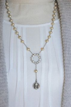 Beautiful Y shaped glass pearl and rhinestone necklace. In the center is a very sparkling and pretty 1920s rhinestone set former pin (pin backing removed). Below it hangs a vintage religious medal from France depicting Mary on one side and the Miracle at Lourdes on the other. The chain is made of beautiful glass pearl style vintage rosary beads with tiny sterling silver chain between the beads and finished off modern link silver tone chain and a modern clasp. So pretty on and neutral enough…