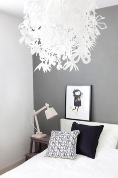 white and grey bedroom with light pink lamp