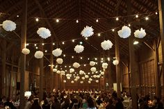 Great combination of festoon lights and pom poms, zig zagged across the barn width