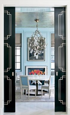 The black and white doors, and the blue, white,pink and orange in the next room is just gorgeous! And that chandelier!