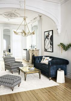 blue velvet upholstered couch, and a low-hanging gold chandelier