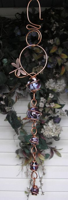 • 10.5 inches long • 14 inches total length with hook • Two 1 inch & three 1/2 inch glass orbs • Hand sculpted copper (semi-precious metal over 99% pure) An amazing handmade creation, express yourself with handmade art! Created with shimmering violet swirl glass orbs nestled within solid hand sculpted copper. Adorned with a copper dragonfly or butterfly. Delightful as a tree charm or suncatcher and perfect displayed indoors or out! Includes a copper hook. Because this art is handmade...
