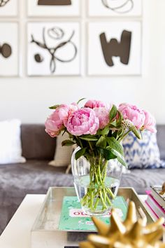 Peonies in glass vase on coffee table