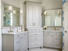 Beautiful bathroom features gray his and hers vanities topped with white marble under gray mirrors illuminated by Reed Single Sconces flanking corner center console cabinet stacked over gray dresser.