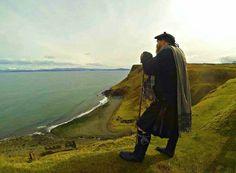 Wearin' a shepherd's maud, fèileadh beag, Balmoral bonnet an' haudin' a cromach in th' Isle of Skye.