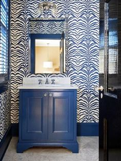 A glossy black door opens to a white and navy powder room featuring white and navy, zebra wallpaper framing navy washstand topped with white marble paired with polished nickel mirror. Zebra Wallpaper, Wallpaper Bathroom Walls, Powder Room Wallpaper, Print Wallpaper, Blue White Bathrooms, White Bathroom Decor, Bathroom Colors, Bathroom Ideas, Bath Ideas
