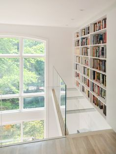 Construct a lovely library Light, bright and elegant, this skinny slice of space has been made into a contemporary library. Natural light floods in through the enormous window, while the glass floor in the mezzanine allows more light to circulate and gives the space a floating feeling.