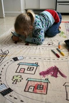 Brilliant! Its a shower curtain (liner) taped to the kitchen floor. The road is drawn on with permanent marker and the kids can color to their hearts content then drive their cars on it.