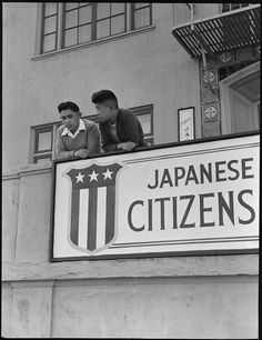 """""""San Francisco, CA. High school boys, on balcony of Japanese American Citizens League at 2031 Bush Street, look down where friends boarded evacuation buses. Evacuees of Japanese ancestry will be housed in War Relocation Authority centers for the duration."""" 4/29/1942 (US National Archives: Dorothea Lange, photographer)"""