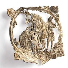 a fragile badge with a medieval scene with knights attacking a priest stamped out of it