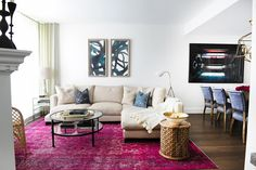 Living room with a bright purple area rug, contemporary art, and a white sectional