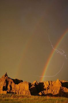 earthstory:    This photo shows the sky above Badlands National Park in South Dakota.The double rainbow appeared in the sky near the end of a thunderstorm. But the storm wasnt quite done and a bolt of lightning ripped though the two rainbows high above the red rocks below.  Keep reading