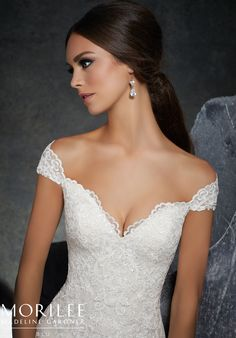 Morilee | Madeline Gardner, Kinley Style 5616 | Classic Fit and Flare Wedding Gown Featuring Frosted Alençon Lace Appliqués on Net. A Romantic Off-the-Shoulder Neckline and Wide Scalloped Hemline Complete the Look. Available in Three Lengths: 55″, 58″, 61″. Colors Available: White, Ivory, Ivory/Champagne