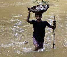 A villager carrying stranded kittens to dry land during floods in Cuttack City, India