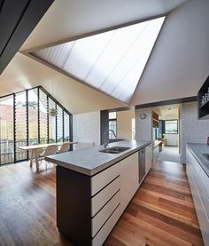 Daylight pours into the kitchen from the angular skylight and through the dining area's large north-facing window.