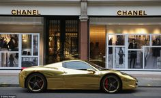 A Gold Ferrari sits outside Chanel on Sloane Street in London as tourists and car enthusiasts flock to the city to catch a glimpse of the world's most expensive cars